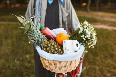 Close up photo of bicycle basket full of fruits,wildflowers and