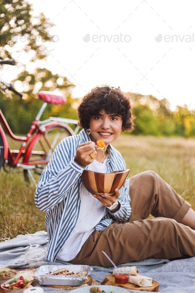 Beautiful smiling girl in striped shirt holding bowl with salad
