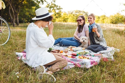 Two beautiful smiling girls sitting with little dog on picnic bl