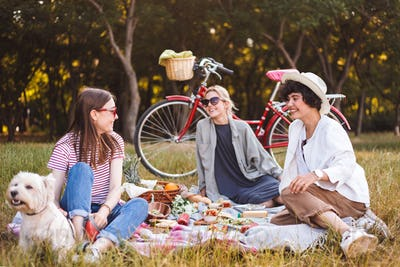 Company of girls happily spending time on beautiful picnic with