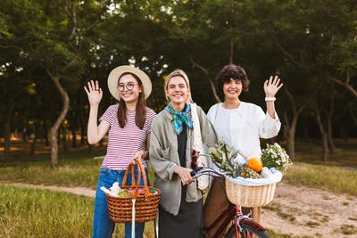 Pretty smiling girls with bicycle and baskets full of wildflower