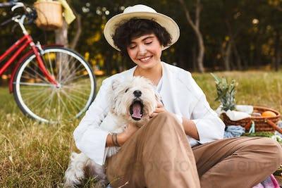 Pretty girl in hat holding cute dog joyfully spending time on pi