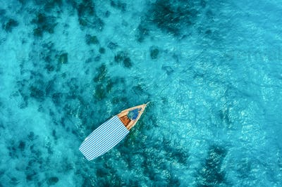 Aerial view of the fishing boat in clear blue water
