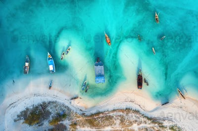 Aerial view of the fishing boats in clear azure water at sunset