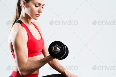 Athletic woman doing fitness workout with dumbbells on gray background.