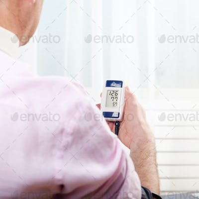 Man read measurement results from personal digital blood pressur