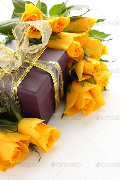 Yellow roses and purple gift box over white