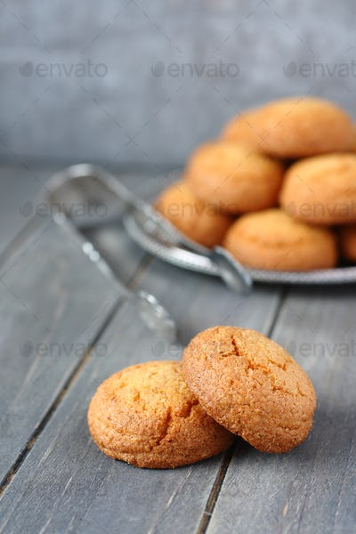 Heap of almond cookies on rustic wooden background