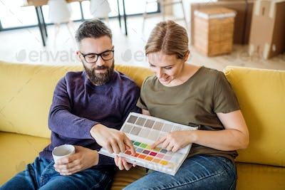 A young couple with color samples sitting on sofa, moving in new home.