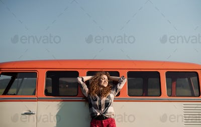 A young girl on a roadtrip through countryside, leaning on a minivan.