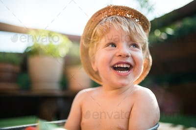 Small boy with a hat outdoors in garden in summer, laughing. Copy space.