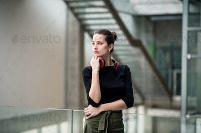 A portrait of young businesswoman with headphones standing in corridor outside office.