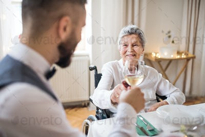 An elderly woman in wheelchair sitting at the table on a indoor party, clinking glasses.