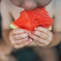 A midsection of small boy in bath outdoors in garden in summer, eating watermelon.