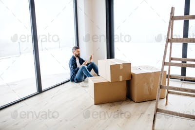 A mature man with cardboard boxes sitting on the floor, furnishing new house.