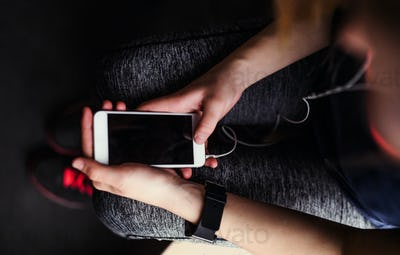 A midsection of young girl or woman with earphones and smartphone in a gym.
