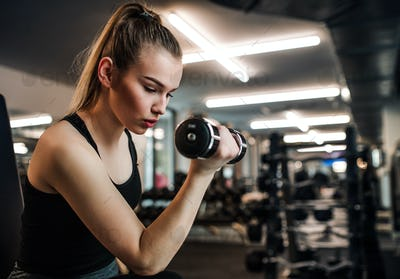 Young girl or woman with dumbbells, doing workout in a gym.