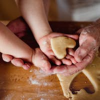 Midsection of grandmother with small toddler boy making cakes at home.