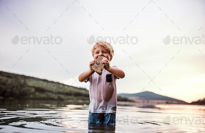A small toddler boy playing outdoors by the river in summer.