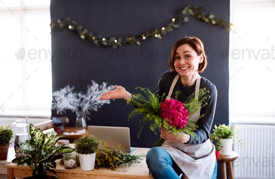 Young creative woman in a flower shop. A startup of florist business.