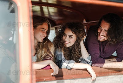 A group of young friends on a roadtrip through countryside, looking out of window.