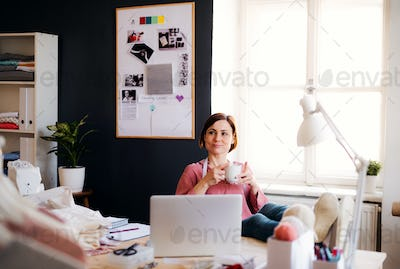 Young creative woman in a studio, resting. A startup of tailoring business.