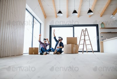 A man and his senior father with VR goggles furnishing new house, a new home concept.