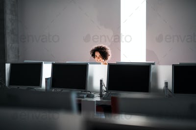 A young student sitting at the desk in a library, using computer.