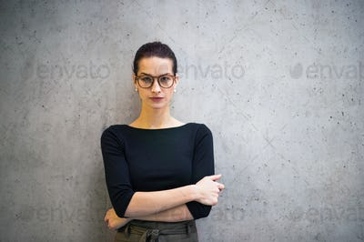 Portrait of young businesswoman with glasses standing in office, looking at camera.