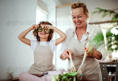A portrait of small girl with grandmother preparing vegetable salad at home, having fun.