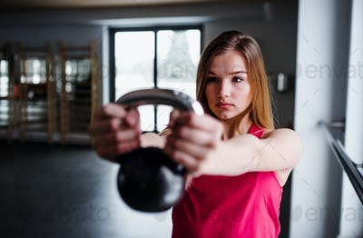 A portrait of young girl or woman doing exercise with a kettlebell in a gym.