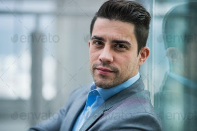 A portrait of young businessman indoors in an office.