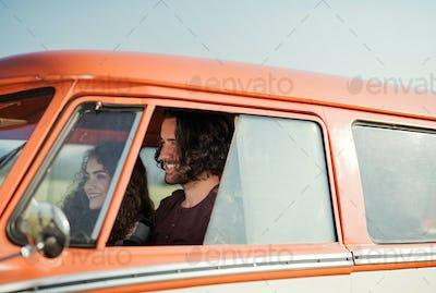 A young couple on a roadtrip through countryside, driving minivan.