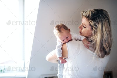 A beautiful young mother with a newborn baby at home. Copy space.