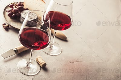 Red wine and cheese on concrete background, copyspace