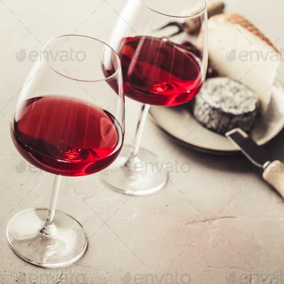 Red wine and cheese on concrete background, close up