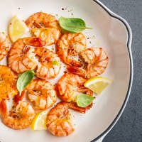 Fried fresh shrimps with spices on white pan