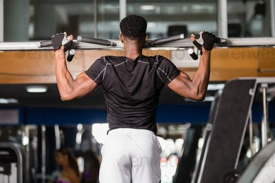 Black African American  young man doing pull up workout at the g