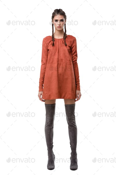 Beautiful young lady standing in ginger suede dress and knee high boots on white background