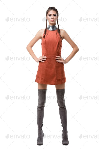 Young pretty lady standing in light brown dress and knee high boots on white background