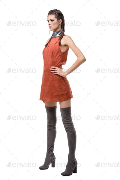 Young lady standing and dreamely looking aside in light brown dress and knee high boots