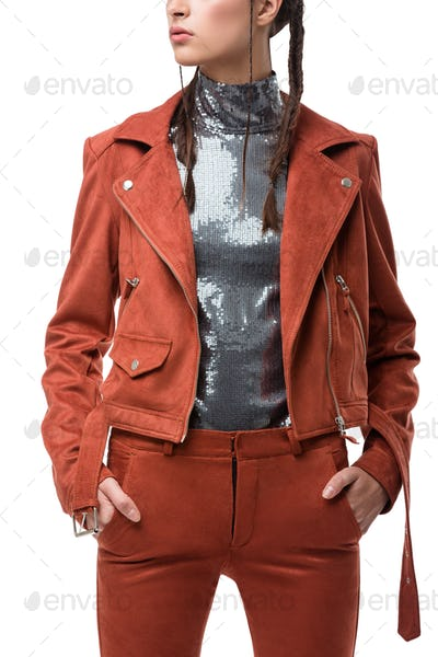 Close up photo of woman body in light brown suede jacket and trousers and silver top with sequins
