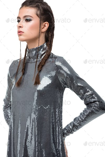 Portrait of young lady standing in dress in sequins and thoughtfully looking aside