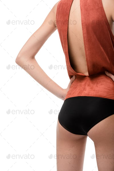 Close up photo of woman body standing from back in light brown top  on white background