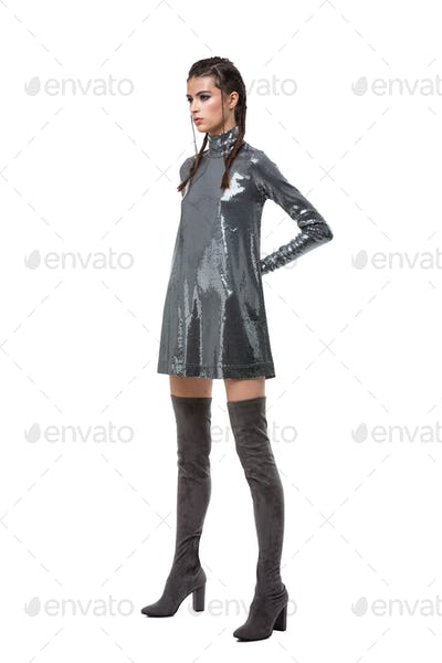 Young pretty lady standing in dress in sequins and knee high boots on white background