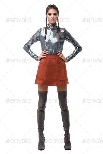 Young beautiful lady standing in light brown skirt and silver top with sequins and knee high boots