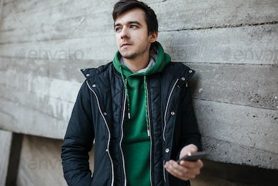 Portrait of guy in green sweatshirt standing on street with cellphone