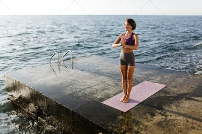 Beautiful woman with dark short hair standing with close eyes and meditating by the sea
