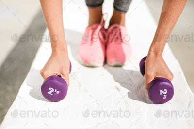 Close up photo of woman hands holding purple dumbbells and legs in pink sneakers