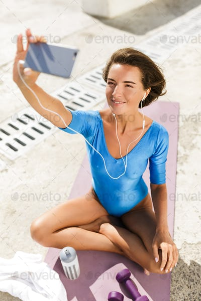 Woman with dark short hair in blue swimsuit sitting on yoga mat and happily looking in her cellphone